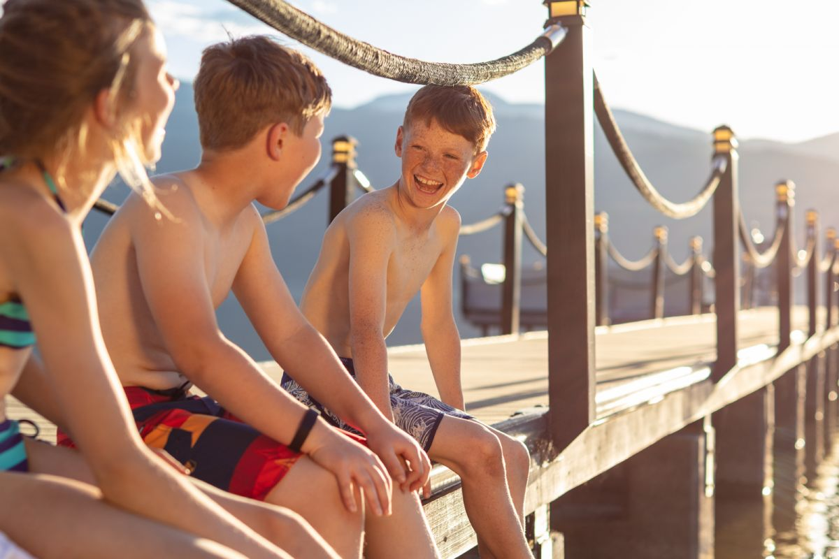 Kids sitting on a dock backlit laughing