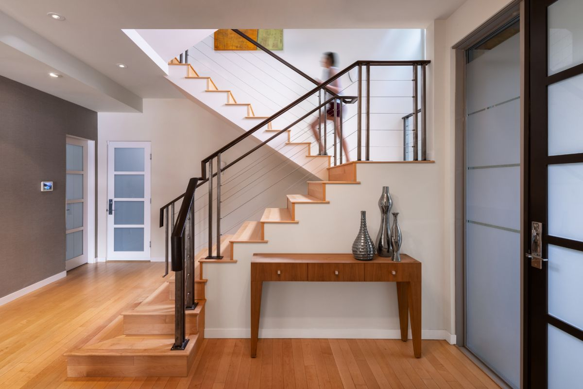 Sothebys architectural photograph by Shawn Talbot of staircase at front entrance of home with person walking up stairs